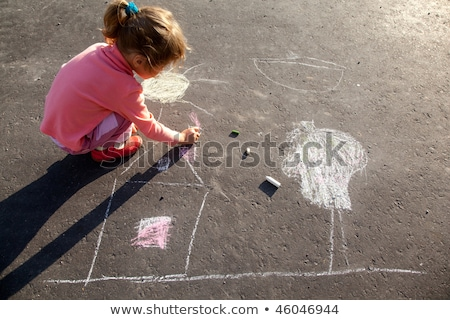 girl sits on concrete asphalt square road. girl draws painting line sun house tree a chalk on asphal Stock photo © Paha_L