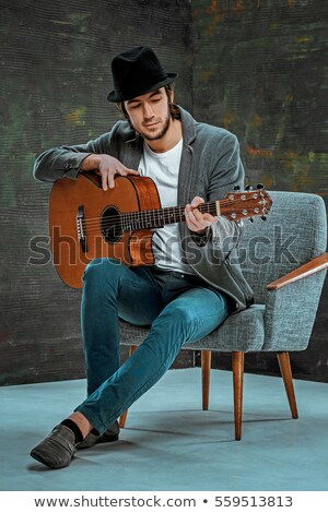 seated young man playing an electric guitar stock photo © feedough