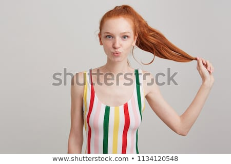 Amusing cute teenage girl in striped top making funny face  Stock photo © deandrobot
