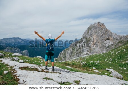 Stock photo: Man on top of mountain with open arms. Conceptual design.