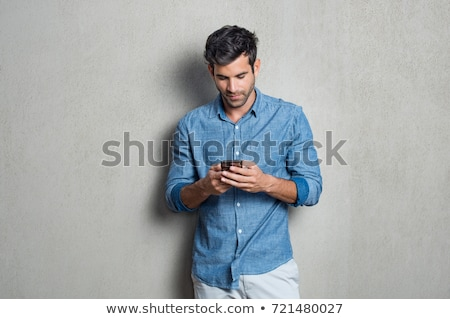 Fiatalember ír szöveges üzenet okostelefon néz képernyő Stock fotó © nyul