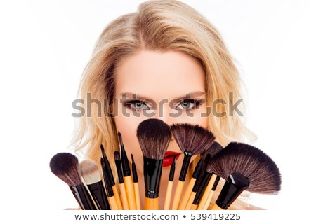 pretty girl with a makeup brush isolated on white background stock photo © nobilior