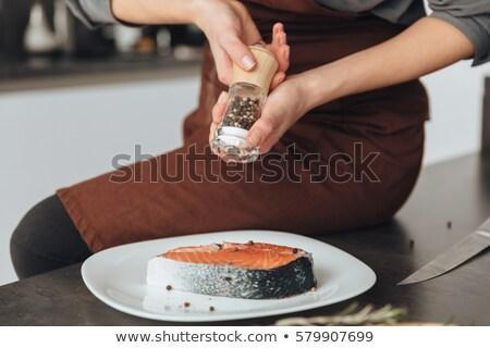 Kép fiatal hihetetlen nő főzés hal Stock fotó © deandrobot