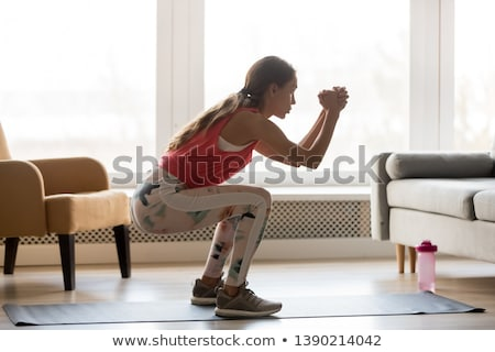 concentrated young strong sports lady make sport exercises stock photo © deandrobot