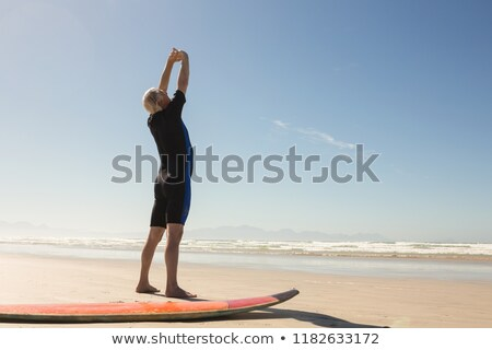 Rear view of man exercising while standing by surfboard Stock photo © wavebreak_media