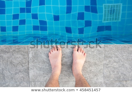 Bare male feet by the poolside Stock photo © stevanovicigor