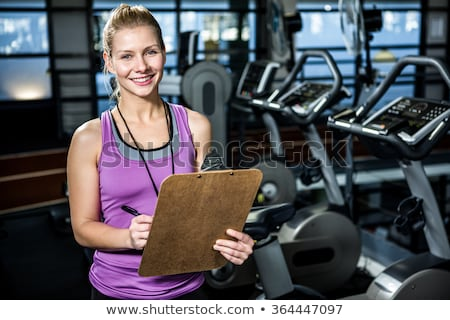 Happy female fitness instructor holding clipboard Stock photo © wavebreak_media