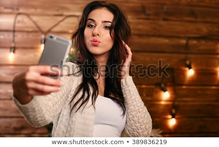 pretty young woman taking selfie with mobile phone in the bed stock photo © boggy
