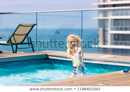 young boy jumping into an infinity pool stock photo © is2