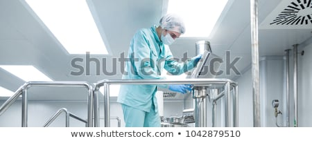 Pharmaceutical factory man worker in protective clothing operate production line in sterile working  Stock photo © Traimak