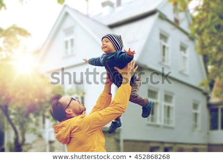 happy father and son over living house in autumn stock photo © dolgachov