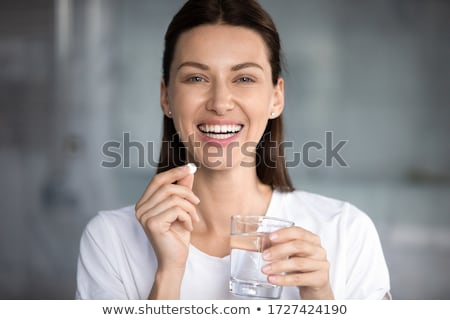beautiful woman in bathroom holding vitamins pills in hands stock photo © deandrobot