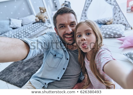 Stock fotó: Cute child making funny face while looking at camera for a family portrait
