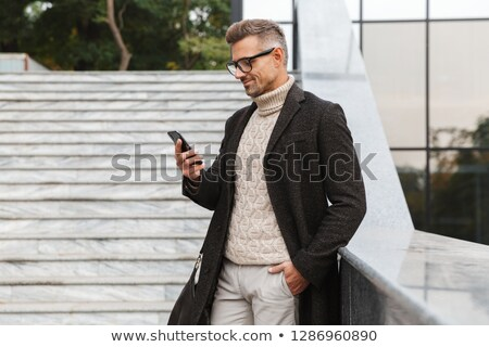 Image of european bearded man in streetwear holding and chatting Stock photo © deandrobot