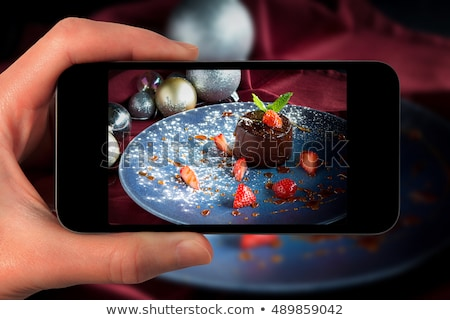 hands photographing food at christmas dinner stock photo © dolgachov