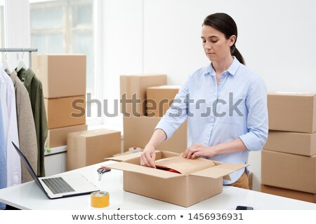 Manager of online shop packing goods into wrapping paper and carton box Stock photo © pressmaster