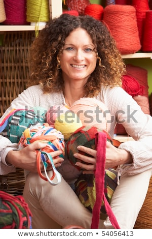 Stock photo: Woman Holding Balls Of Wool Sitting In Front Of Yarn Display