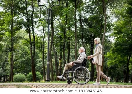 Side view of disabled senior man and senior woman walking on promenade at beach Stock photo © wavebreak_media