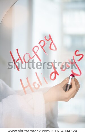 Hand of young female in white bathrobe writing regards with lipstick Stock photo © pressmaster