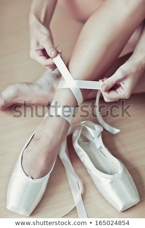Ballet dancer tying slippers around her ankle Stock photo © boggy