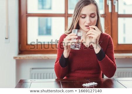 Woman taking some medicine or pill against her migraine Stock photo © Kzenon