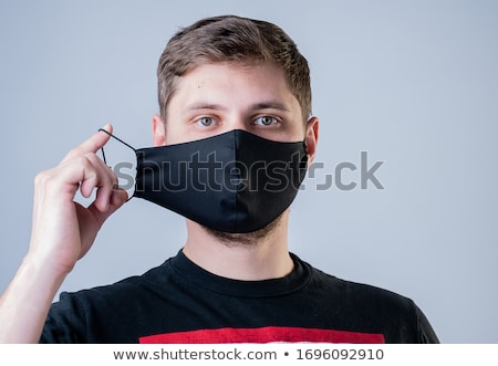 Serious infected man wears protective mask, cares about health d Stock photo © vkstudio