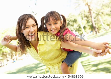 mother giving daughter piggy back ride at summer park. Stock photo © Nobilior