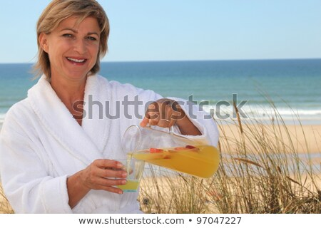 Woman pouring herself a glass of orange juice at the beach Stock photo © photography33