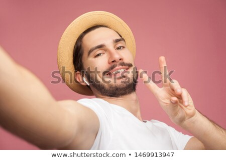 handsome young casual man talking on the phone and showing victory sign while smiling at the camera stock photo © feedough