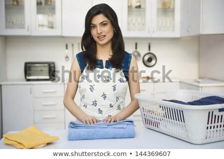 Young woman folding towel with laundry basket Stock photo © wavebreak_media