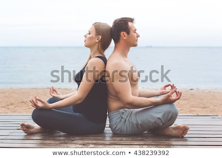 healthy man doing pilates yoga meditation on beach summer Stock photo © juniart