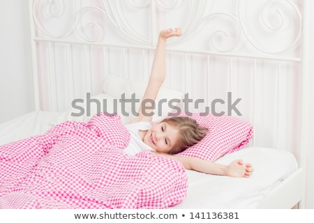 pretty blonde female waking up lying in bed stock photo © deandrobot