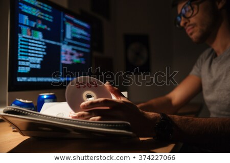 Confident programmer taking cd with data base and coding  Stock photo © deandrobot