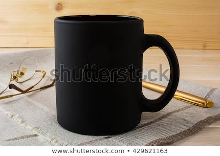 Black Coffee Mug Mockup With Glasses And Pen Photo stock © TasiPas