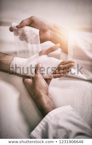 Physiotherapist putting bandage on injured hand of patient Stock photo © wavebreak_media
