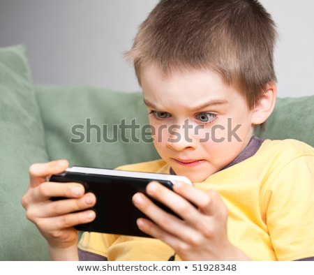 Young boy playing with handheld game Stock photo © IS2