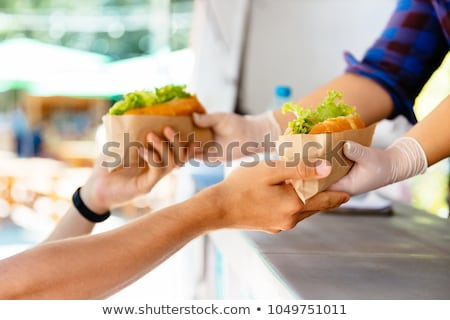 close up of hands with fast food on street Stock photo © dolgachov