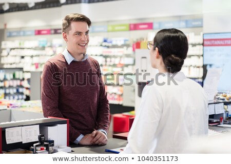 pharmacist answering question of a young customer in a modern dr Stock photo © Kzenon