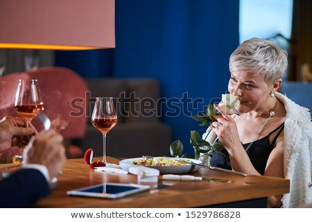 mature woman is offered a rose stock photo © is2