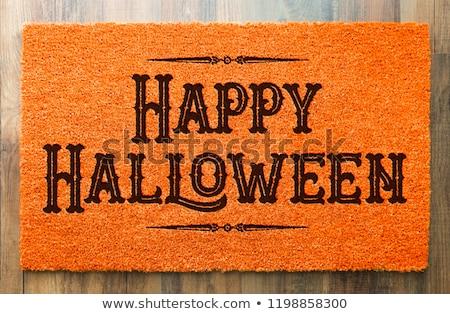 happy halloween orange welcome mat on wood floor background stock photo © feverpitch