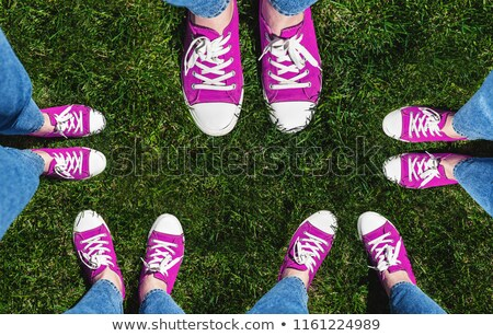 Legs in old pink sneakers on green grass. View from above. The c Stock photo © TanaCh