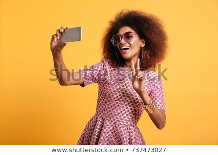african woman posing isolated over yellow background take a selfie by mobile phone showing thumbs up stock photo © deandrobot