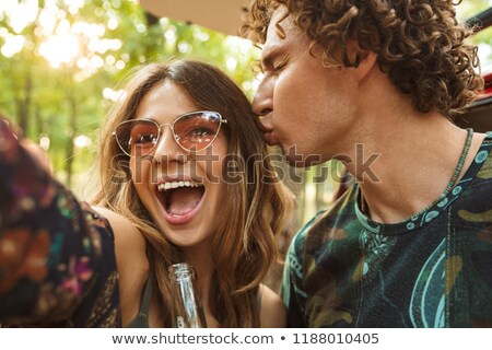 Photo of cheerful hippie couple man and woman rejoicing, and tak Stock photo © deandrobot