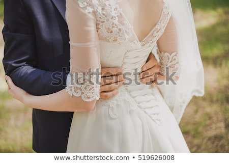 Tender beautiful bride's hands on elegant white wedding dress closeup Stock photo © ruslanshramko