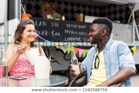 mixed race couple eating and talking at food truck Stock photo © dolgachov