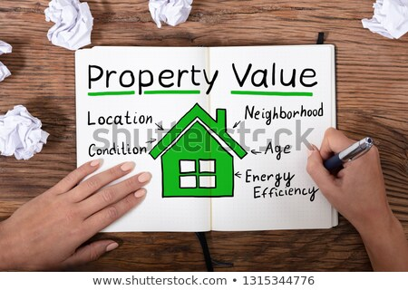 Woman's Hand Writing Property Value On Notebook Stock photo © AndreyPopov
