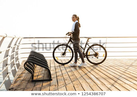 Photo of beautiful woman standing with bicycle on boardwalk, dur Stock photo © deandrobot