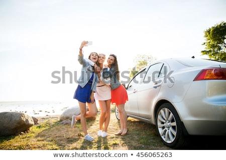 happy teenage girls or women near car at seaside Stock photo © dolgachov