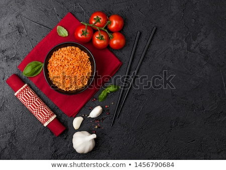 black plate bowl of rice with tomato and basil and garlic and chopsticks on red bamboo place mat on stock photo © denismart