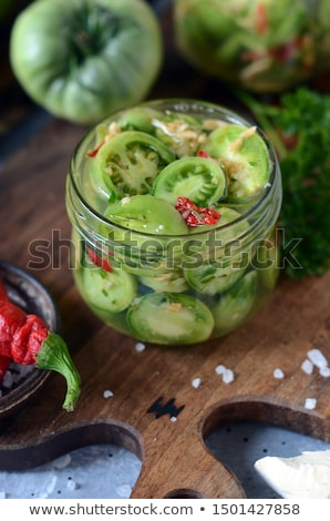 glass jar with pickled green tomatoes prepared for winter Stock photo © Melnyk